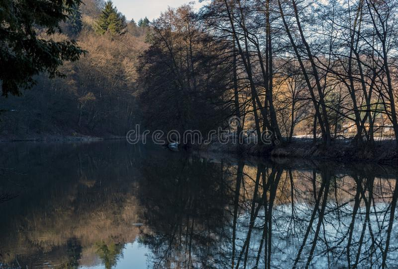 Shadows of trees on the banks of the river reflecting on the surface. At noon royalty free stock photos