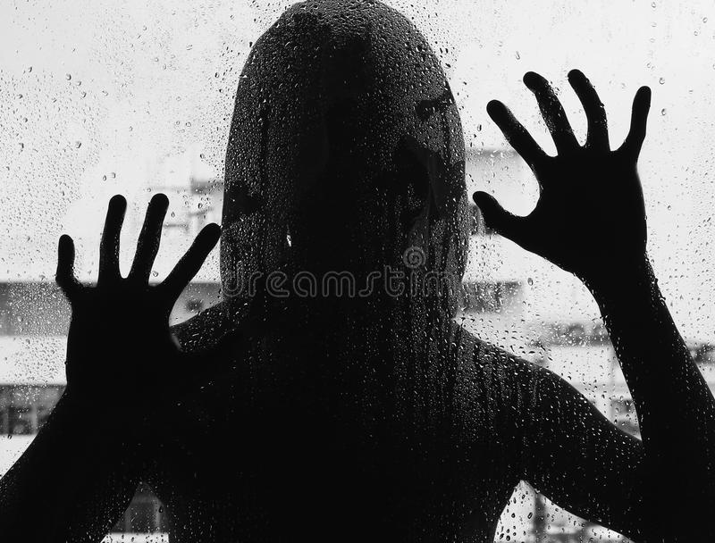Shadowy figure with a knife behind glass stock photos