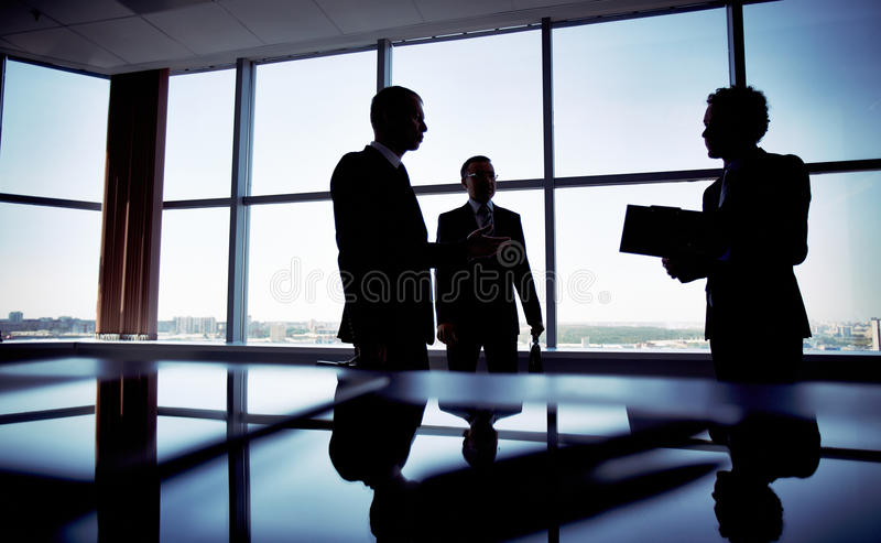 Shady business. Shady image of a manager discussing business matters with her subordinates stock photo
