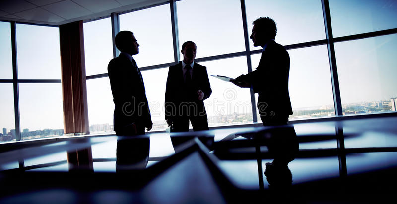 Shady business. Shady image of a manager discussing business matters with his subordinates stock image