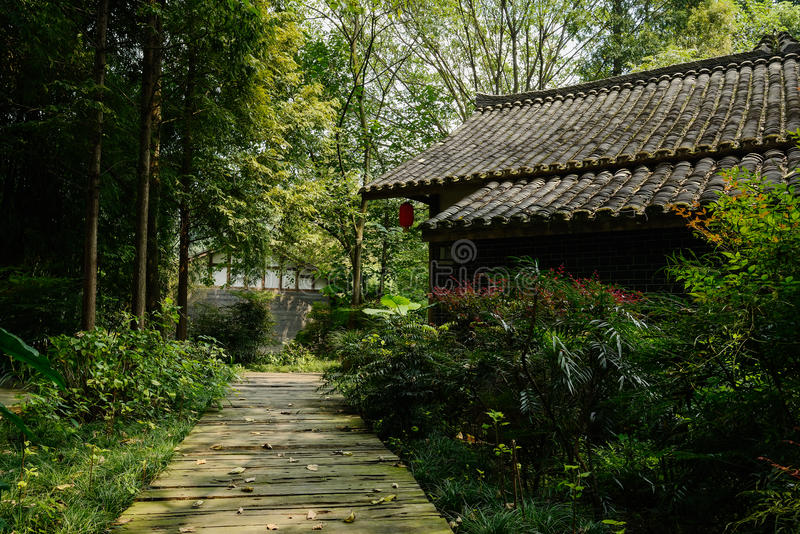 Shady planked path before Chinese old building in sunny autumn stock photography