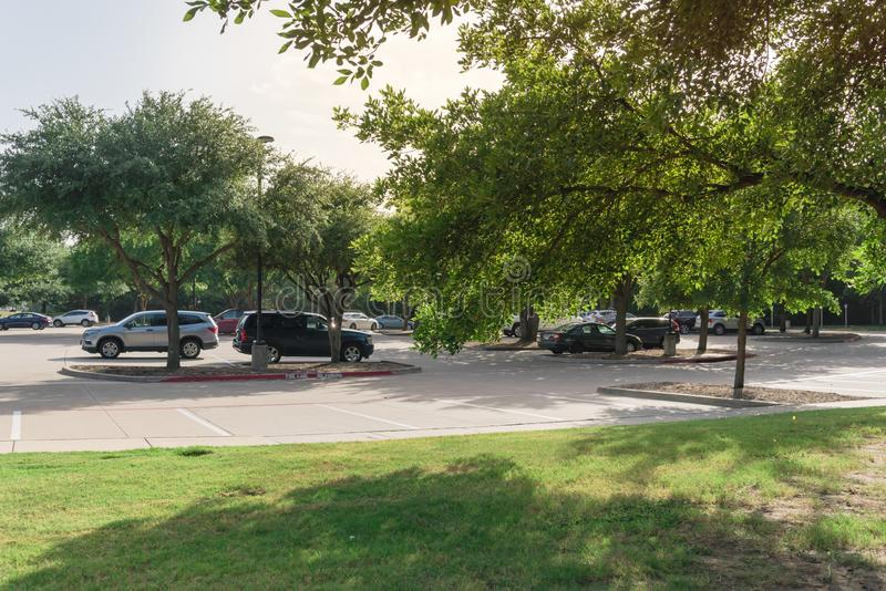 Shady public parking lot in Texas, USA. Cars parked under the tree shade at large public parking in Coppell, Texas, USA royalty free stock photography