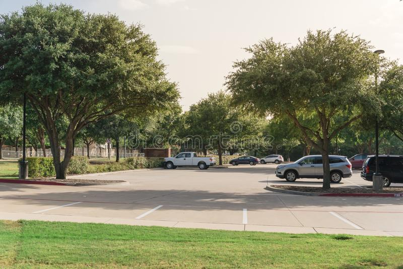 Shady public parking lot in Texas, USA. Cars parked under the tree shade at large public parking in Coppell, Texas, USA royalty free stock photo