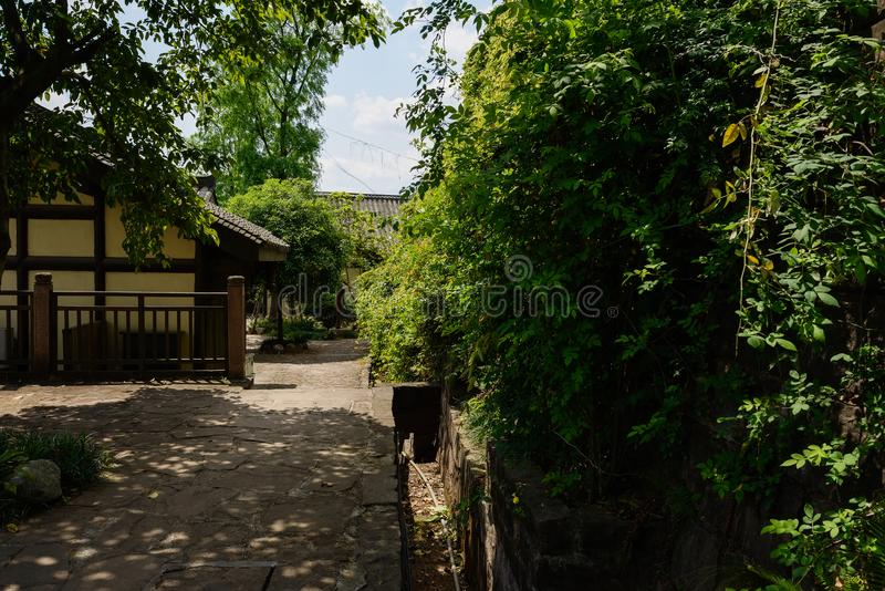 Shady stone path before Chinese traditional houses in sunny spring afternoon. Shady stone-paved path before traditional buildings in sunny spring afternoon stock photo