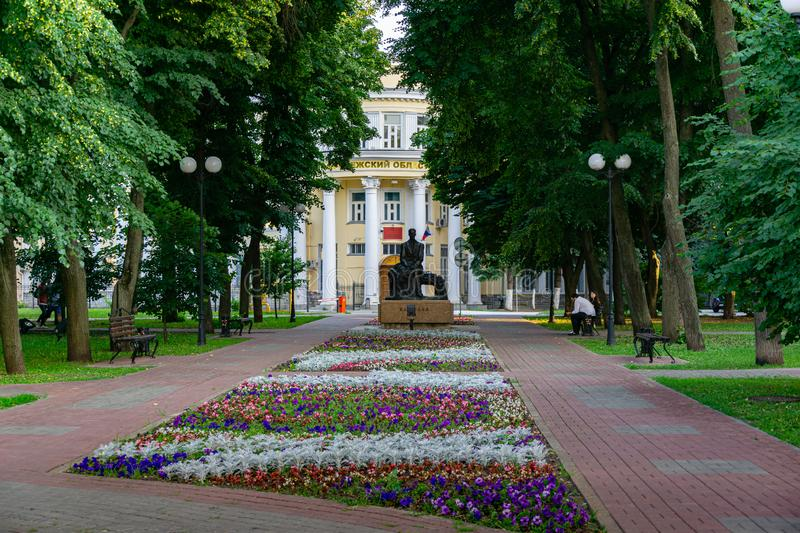 Shady street with beautiful flower bed and monument to Bunin stock photo