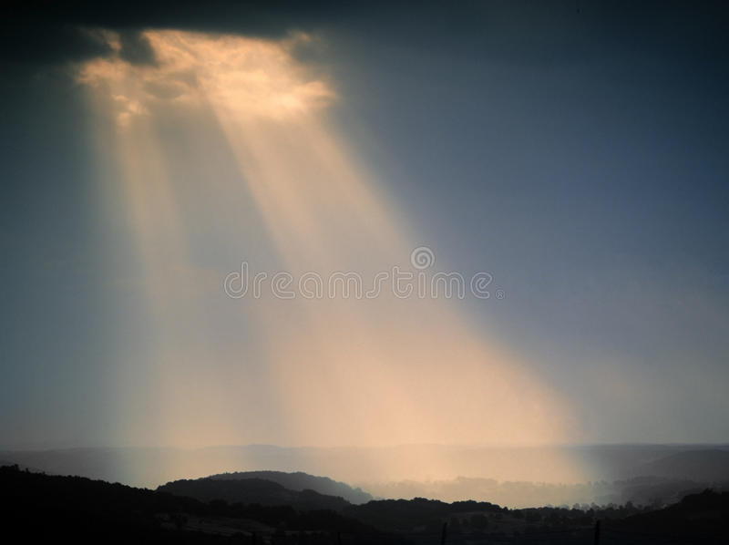 Shaft of light. Cloudburst and sunburst, a shaft of light from clouds over a landscape royalty free stock photos