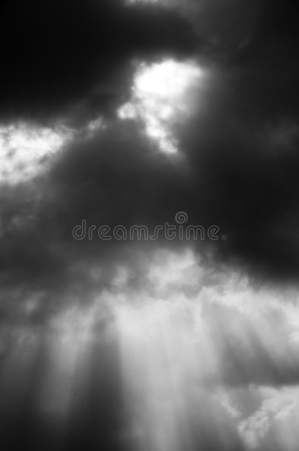Shafts of light. Pierce through dark clouds black and white stock photography