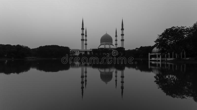 Shah alam, Μαλαισιανό τζαμί κατά τη διάρκεια της ανατολής του ηλίου με αντανάκλαση από τη λίμνη στοκ εικόνα