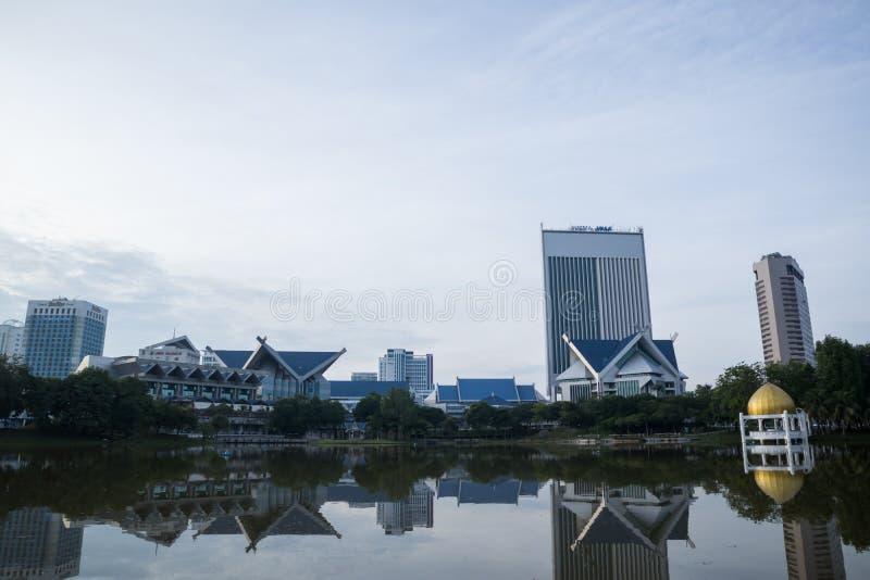 Shah Alam cityscapesikt i morgonen med reflexion i sjön royaltyfri bild
