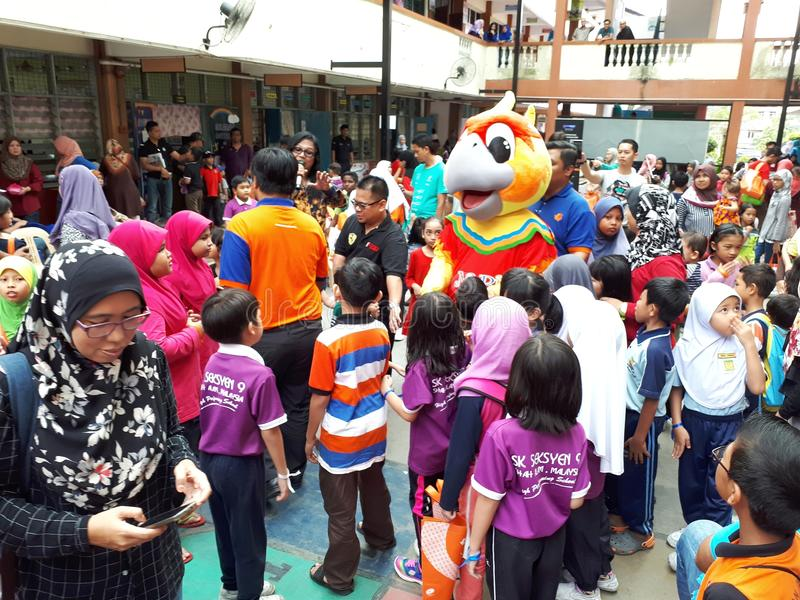 SHAH ALAM, MALAYSIA - AUGUST 12, 2017: Crowds of peoples with a mascot and an artist during BREAK THE COIN BOX PROGRAM. royalty free stock photo