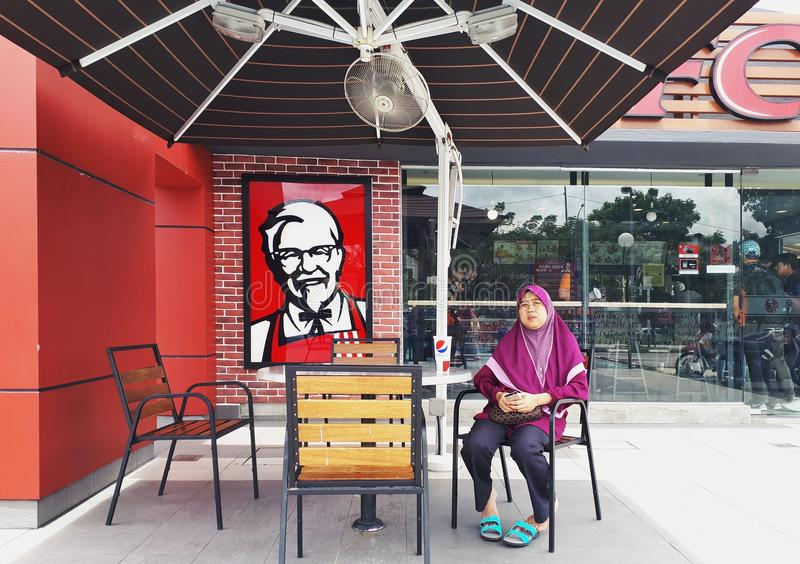 SHAH ALAM, MALAYSIA - AUGUST 13, 2017: A women sit on the chair outside of the famous fast food restaurant Kentucky Fried Chicken. royalty free stock image