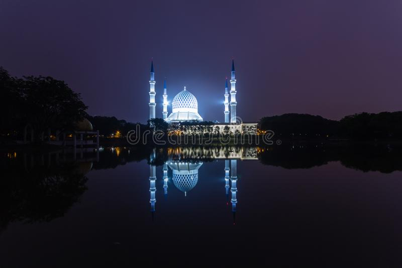 Shah alam, malaysia mosque during sunrise with reflection from the lake. Calm and beautiful view at shah alam, malaysia mosque during sunrise with reflection royalty free stock image