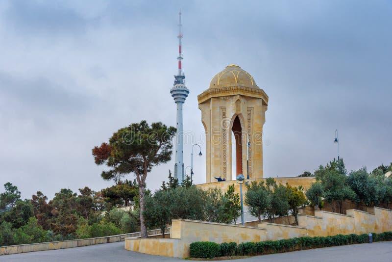 Shahidlar纪念碑或永恒火焰纪念碑在受难者`车道 并且电视塔在晚上 秃头 阿塞拜疆 免版税库存照片