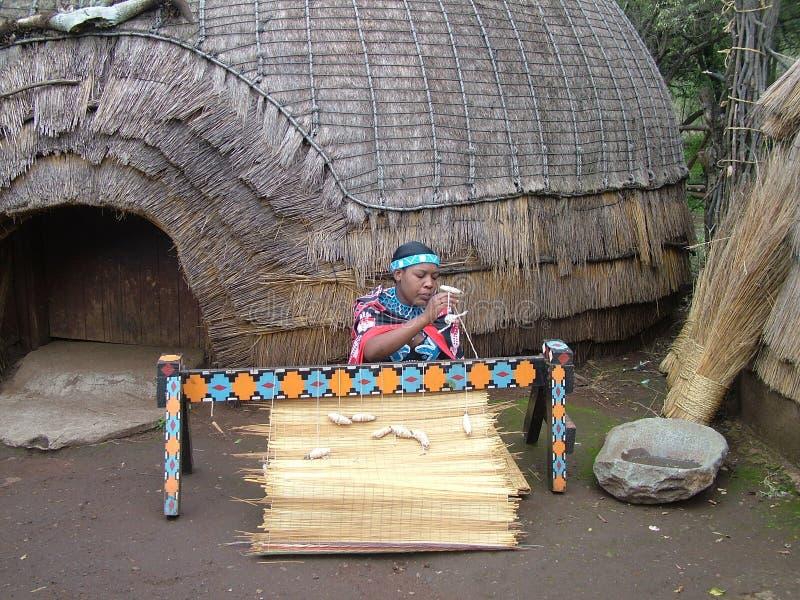 Shakaland,南非-大约2011年11月:未认出的祖鲁族人妇女编织一张席子 库存图片