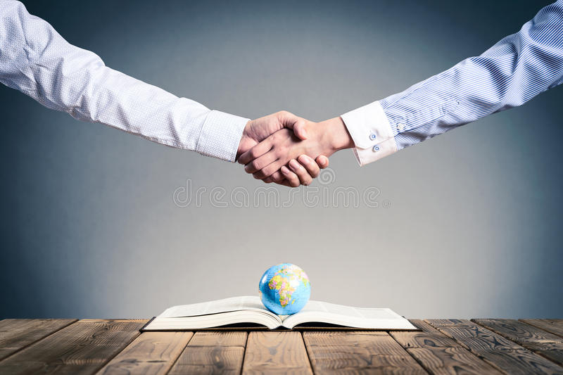 Shake hands on a miniature globe royalty free stock photography