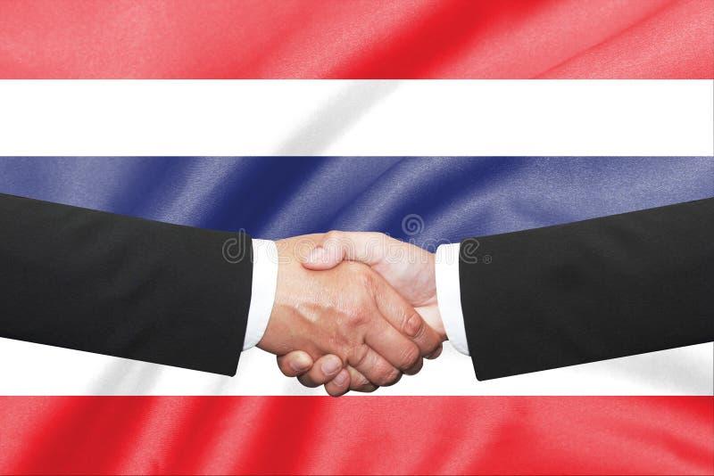 Shakehand d'homme d'affaires au-dessus de fond thaïlandais de drapeau photo stock