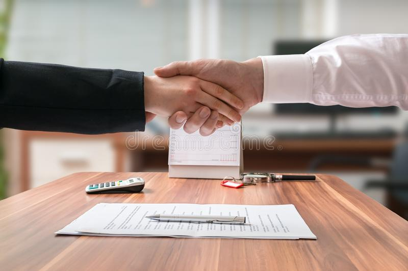 Shakehand of lawyer and business woman sitting behind desk with agreement.  royalty free stock image