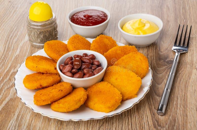 Shaker med peppar, bunkar med ketchup, majonnäs, stekt kycklingklumpar, bunke med den röda bönan i plattan, gaffel på trätabellen arkivfoto