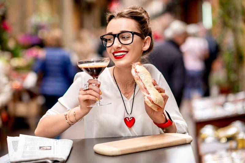 Shakeratodrank met panini en krant stock foto's