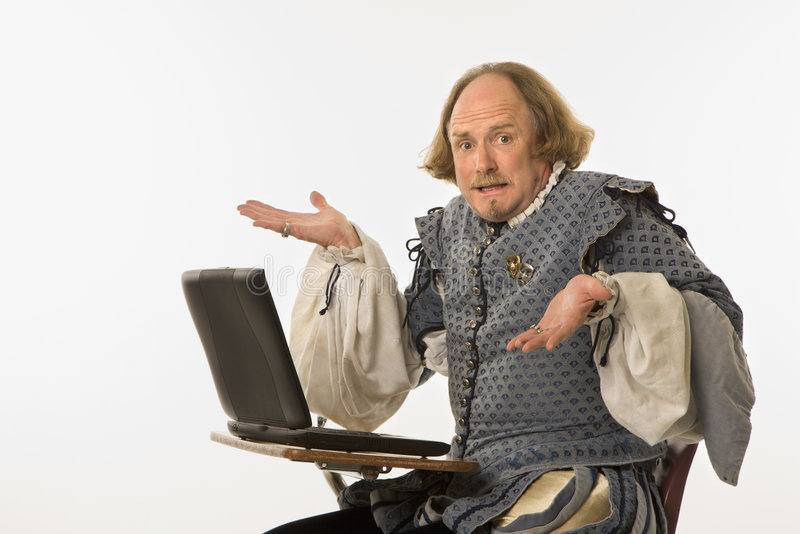Shakespeare with computer. William Shakespeare in period clothing sitting in school desk with laptop computer shrugging at viewer