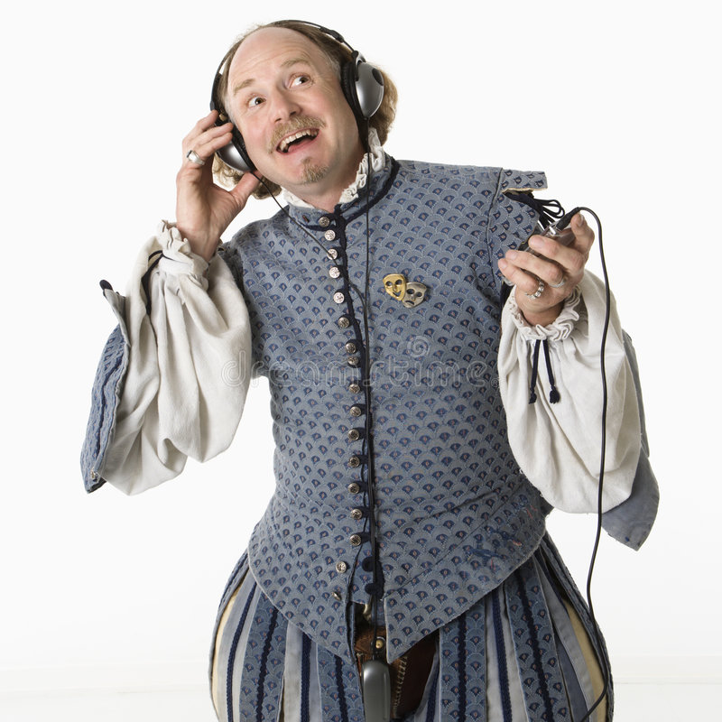 Shakespeare listening to music. William Shakespeare in period clothing listening to mp3 player and smiling royalty free stock photo