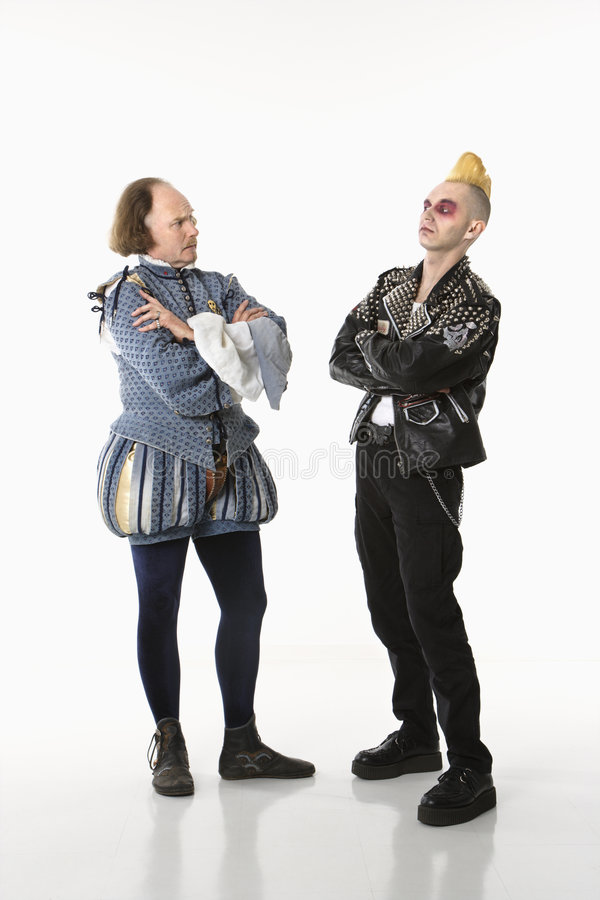 Shakespeare and punk man. William Shakespeare in period clothing and gothic punk young man standing face to face with arms crossed stock photography