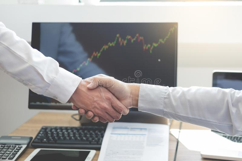 Shaking Hand between businessman of cooperation over Stock market chart, business trading concept.  stock image