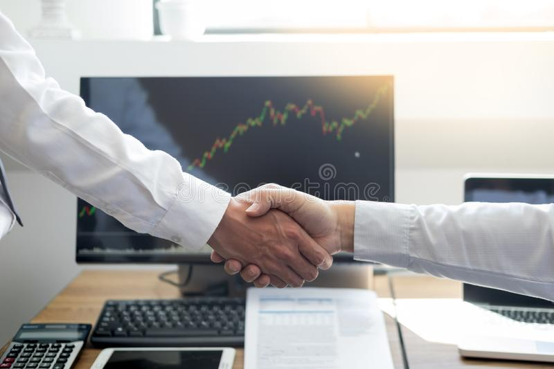 Shaking Hand between businessman of cooperation over Stock market chart, business trading concept. Shaking Hand between businessman of cooperation over Stock stock photos