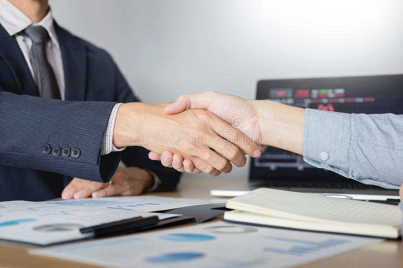 Shaking Hand between businessman of cooperation over Stock market chart, business trading concept stock image