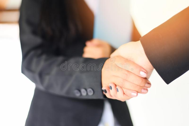 Shaking hand concept - two successful asian business women shake hands people in need of exchange and cooperation finishing up royalty free stock photo