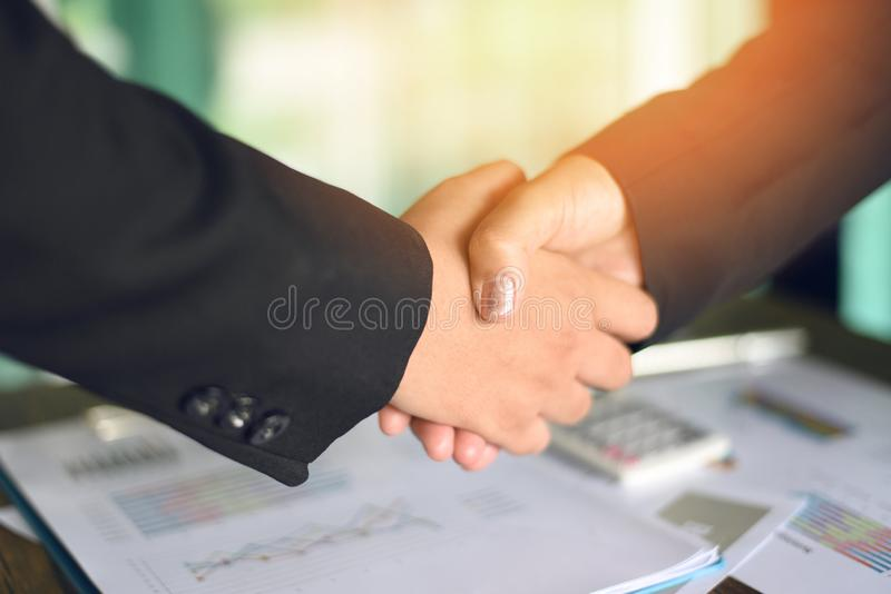 Shaking hand concept - two successful asian business women shake hands people in need of exchange and cooperation finishing up royalty free stock images