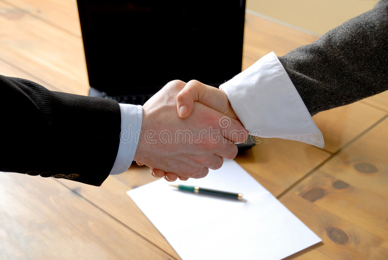 Shaking hands. Man and woman shaking hands in front of laptop