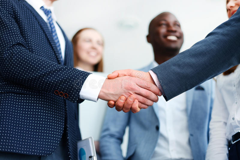 Shaking hands. Business people shaking hands, finishing up a meeting royalty free stock images