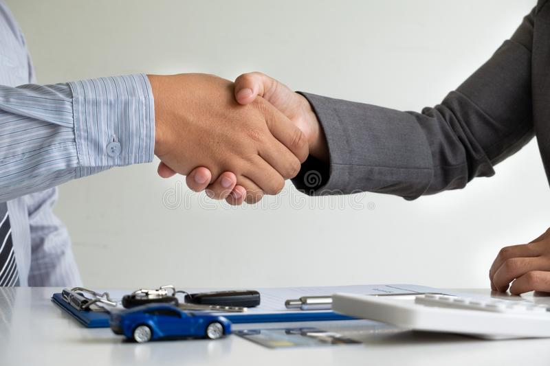 Shaking hands, Car dealership provides advice about insurance details and car rental information and delivers the keys. After signing the rental contract royalty free stock photography