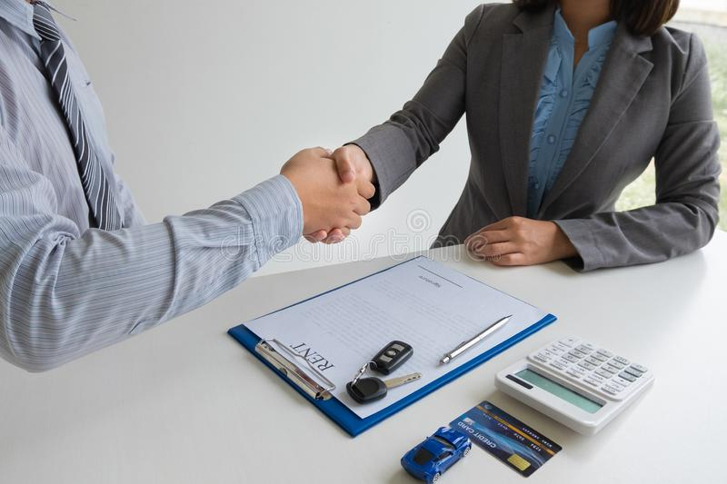 Shaking hands, Car dealership provides advice about insurance details and car rental information and delivers the keys. After signing the rental contract royalty free stock photo