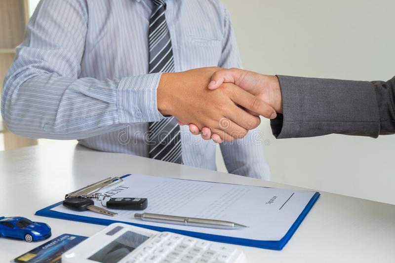 Shaking hands, Car dealership provides advice about insurance details and car rental information and delivers the keys. After signing the rental contract royalty free stock photos