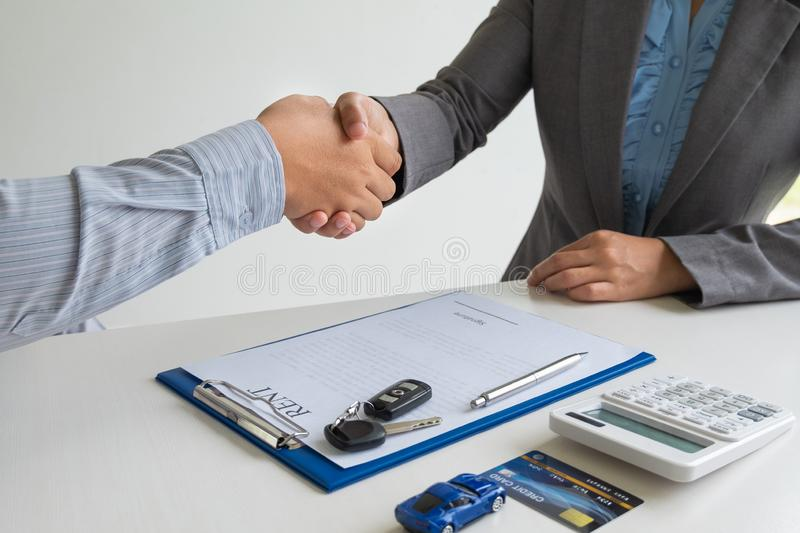 Shaking hands, Car dealership provides advice about insurance details and car rental information and delivers the keys. After signing the rental contract stock photography