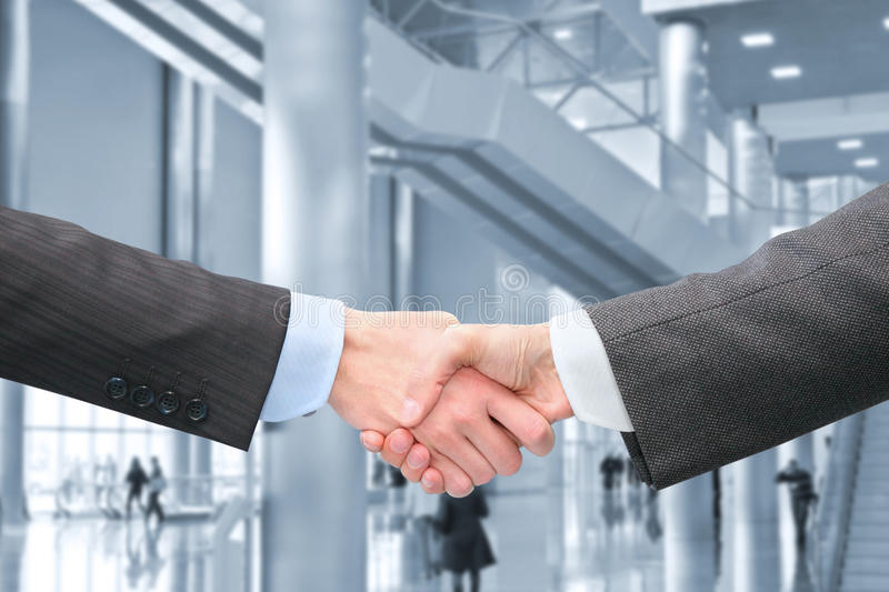 Shaking hands in hall of business center royalty free stock images