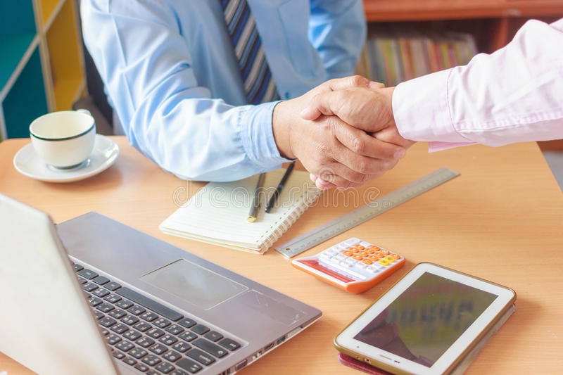 Shaking hands at a meeting. Two Confident businessman sitting at the negotiating table in the office and shaking hands close-up view of hands. Business people royalty free stock photography