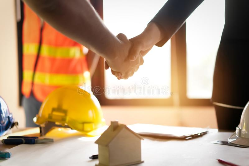 Shaking hands over the table of two  business men. Successful after complete conversation about house building and construction topic. Business achievement stock photo