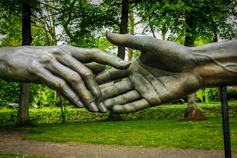 Shaking hands statue. Bronze statue of two hands shaking in outdoor environment stock photo