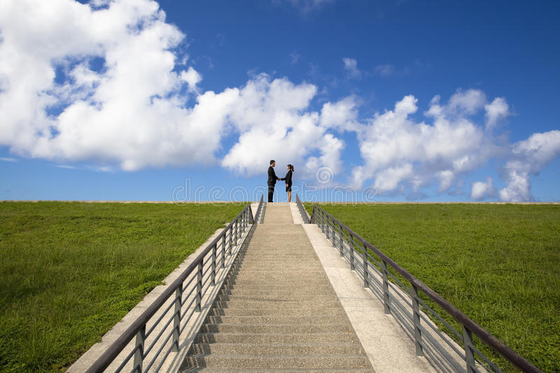 Shaking hands on the top of stairs royalty free stock image