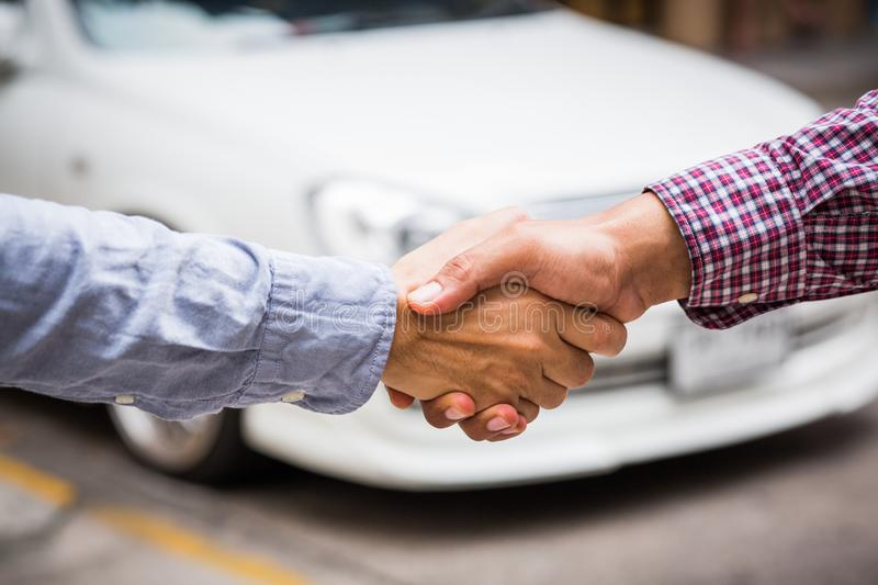 Shaking hands on car background. royalty free stock photo