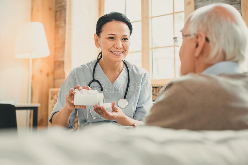 Smiling kind lady holding white bottle with pills. Shaking out medications. Smiling kind lady holding white bottle with pills having appointment with grey-haired stock image