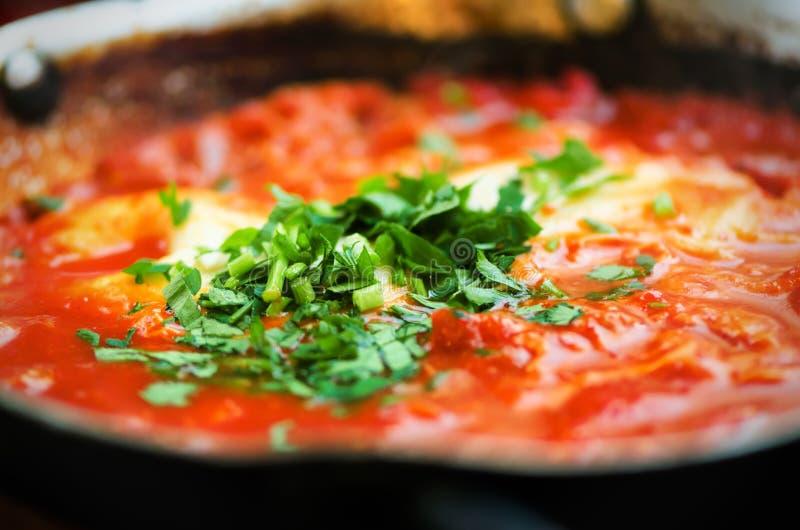 Shakshuka Традиционная еврейская еда и ближневосточный рецепт кухни Яичницы, томаты, болгарский перец и петрушка в a стоковые фотографии rf