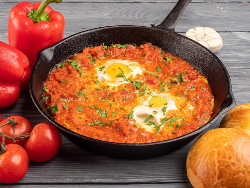 Shakshuka with bell pepper, tomatoes, hummus and rolls stock images