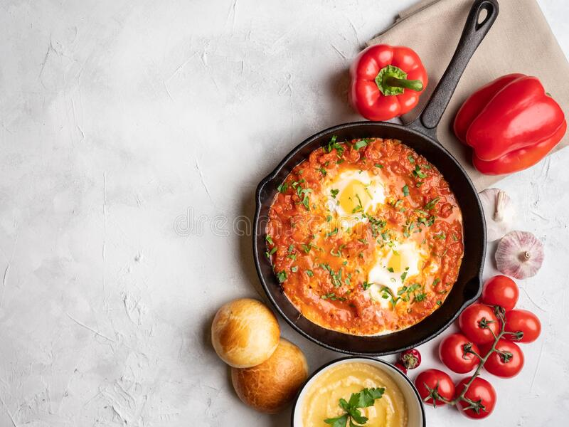 Shakshuka with bell pepper, tomatoes, hummus and rolls. Top view, place for text royalty free stock photography