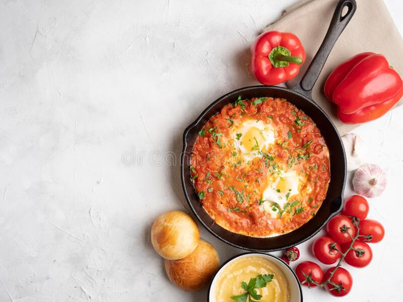 Shakshuka with bell pepper, tomatoes, hummus and rolls. Top view, place for text royalty free stock photo