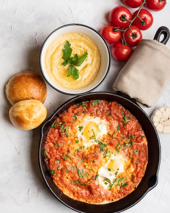 Shakshuka with bell pepper, tomatoes, hummus and rolls. Top view, place for text royalty free stock photos