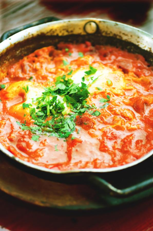 Shakshuka Comida judía tradicional y receta de Oriente Medio de la cocina Huevos fritos, tomates, paprika y perejil en a imagenes de archivo